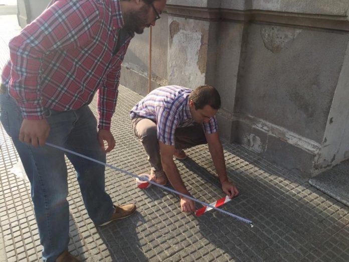 Un municipio pone cintas en el suelo para marchar distancias afuera de los bancos