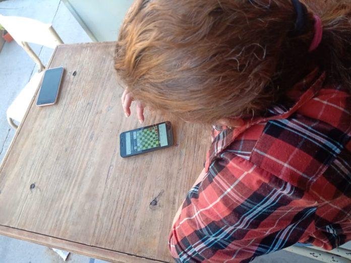 Una interna participa en el torneo de ajedrez con su celular. (Prensa SPB)