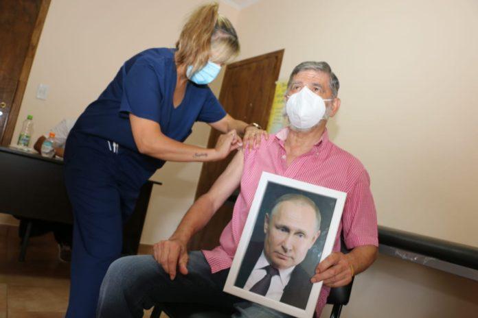 El intendente de Roque Pérez volvió de su licencia y recibió la vacuna abrazado a una foto de Putin