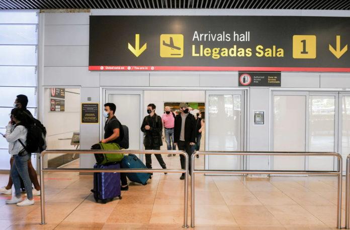 Viajeros hacen cola en el aeropuerto internacional de Bajaras, en Madrid. (El País)