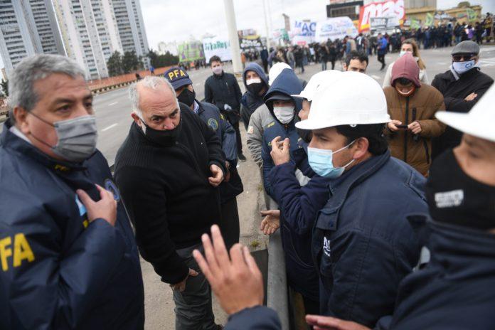 Efectivos policiales dialogan con los trabajadores en el Puente Pueyrredón. (Télam)